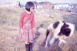 Photograph of a girl with a red dress and a dog in Nain, Newfoundland and Labrador