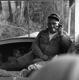 Photograph of a man in coveralls smoking a cigar