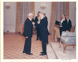 Photograph of Governor General Roland Michener presenting Thomas Head Raddall with the Medal of S...