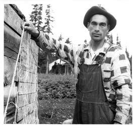Photograph of an unidentified man wearing a plaid shirt and holding a seal net