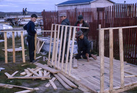 Photograph of four boys building a small house together