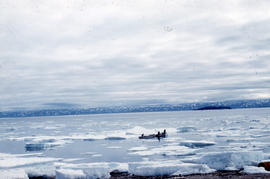 Photograph of two small boats and ice floes in Frobisher Bay