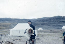 Photograph of a girl holding a dog in Cape Dorset, Northwest Territories