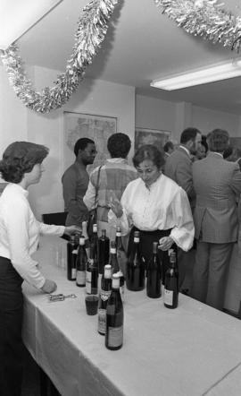 Photograph of two people with wine bottles at the opening of the Ocean Studies house