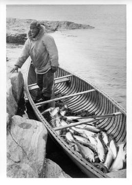 Photograph of an unidentified man standing in a boat full of fish