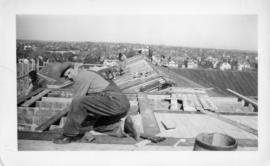 Photograph of men working on the roof of the Arts & Administration Building