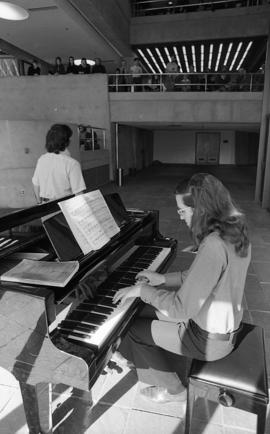 Photograph of an unidentified person playing the piano in the Dalhousie Arts Centre