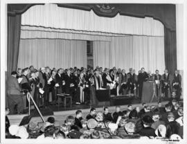 Photograph of scientists and guests on stage gathered around Chancellor C.D. Howe