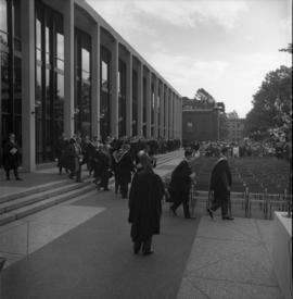 Photograph of a convocation procession in front of the Tupper Building