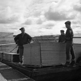 Photograph of three men with supplies on a barge on the Koksoak River