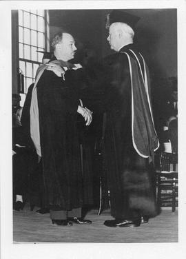 Photograph of Dr. Ross Flemington conferring an honorary degree on Henry Hicks