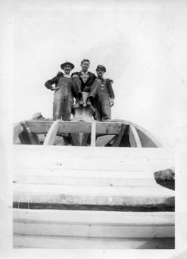 Photograph of three men standing on top of the Arts & Administration Building