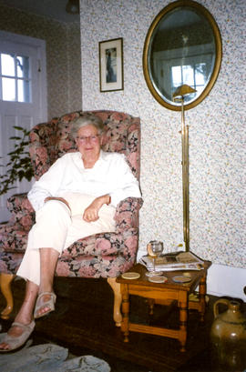 Photograph of Barbara Hinds sitting in a floral armchair