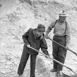 Photograph of a woman and a man with shovels