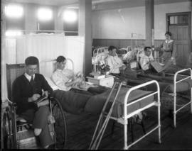 [Convalescing soldiers sewing, embroidering, weaving in bed and a wheelchair with nurse watching ...