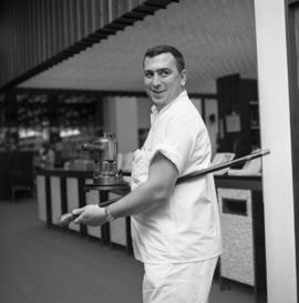 Photograph of an unidentified person with a coffee pot and a walking stick