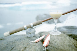 Photograph of a fishing rod, a glass, and fish hooks