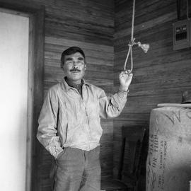 Photograph of a man with one eye ringing the bell at the St. Stephen's Anglican church in Fort Ch...
