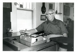 Photograph of Thomas Head Raddall sitting at his desk with a typewriter