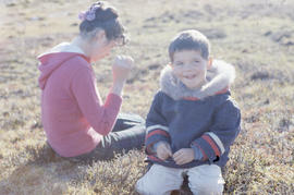 Photograph of Allie and Sam sitting outdoors in Cape Dorset, Northwest Territories