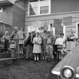 Photograph of children holding signs about a bus