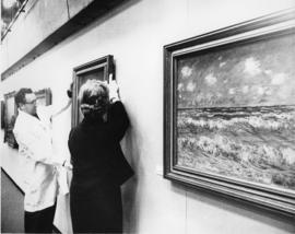 Photograph of unidentified man and Evelyn Holmes installing a painting