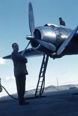 Photograph of Clare Dobbin standing by a plane in Frobisher Bay, Northwest Territories