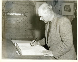 Photograph of Thomas Head Raddall signing the register of the Habitation at Lower Granville after...