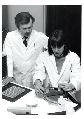 Photograph of two individuals running an experiment, one holding a machine