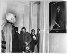 Photograph of an unidentified person looking at a portrait