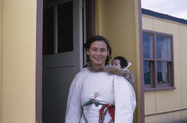 Photograph of Joanna Koneak standing in a doorway while carrying a baby on her back