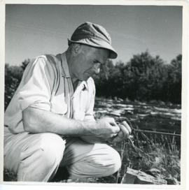 Photograph of Thomas Head Raddall untangling a fishing lure near Trout Rock, at the foot of Lake ...