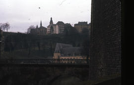 Photograph of buildings and a church from across an unidentified bridge