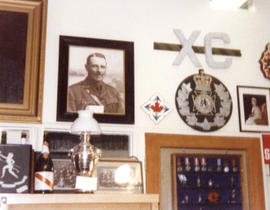 Photograph of a museum display of Royal Winnipeg Rifles Regiment artifacts including a portrait o...