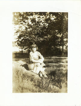 Photograph of a young woman sitting in the grass