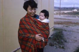 Photograph of a woman holding a baby in a plaid shawl and smoking a cigarette
