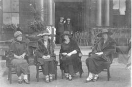 Photograph of four unidentified people sitting in chairs in front of Halifax city hall