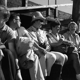 Photograph of five unidentified people sitting in a row