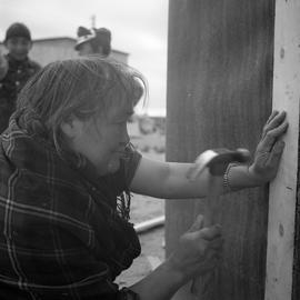 Photograph of Alicie Berthé hammering a nail into her house in Fort Chimo, Quebec