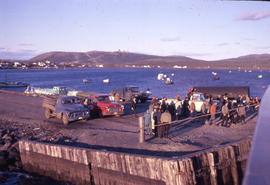 Photograph of several people and trucks on a pier in Cartwright, Newfoundland and Labrador