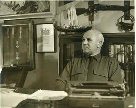 Photograph of Thomas Head Raddall sitting at his desk in his study with a bookshelf and decorativ...