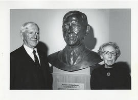 Photograph of Norman A. M. MacKenzie with a bust of himself and an unidentified woman