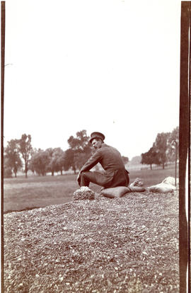 Photograph of an officer in uniform sitting on a sandbag at what might be Reach Field in Hythe, E...