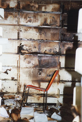 Photograph of fire damaged shelves, wall and documents