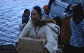 Photograph of an unidentified woman carrying a box