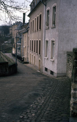 Photograph of a narrow, downhill street and buildings