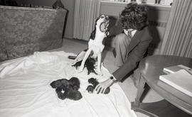 Photograph of an unidentified person with a dog and puppies at Howe Hall