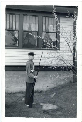 Photograph of Arthur White standing in profile, dressed in period uniform, and holding a rifle an...