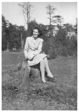 Photograph of an unidentified person sitting on a tree stump