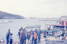 Photograph of several people standing on the shore of Battle Harbour, Newfoundland and Labrador